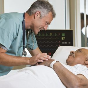 doctor leaning over a man in a hospital bed