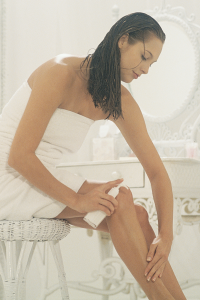 Woman putting lotion on her legs