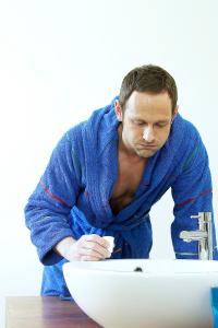man gargling at a sink